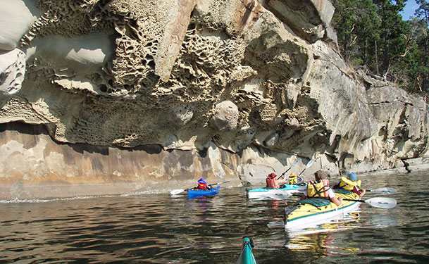group paddling beside rock formation